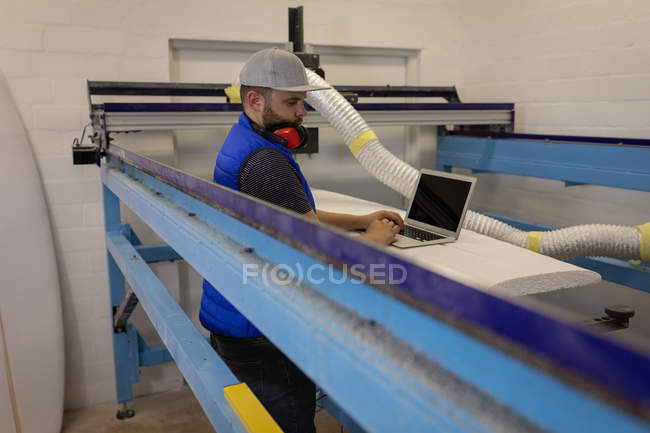 Side view of Caucasian man with earmuffs around the neck using laptop in workshop — Stock Photo
