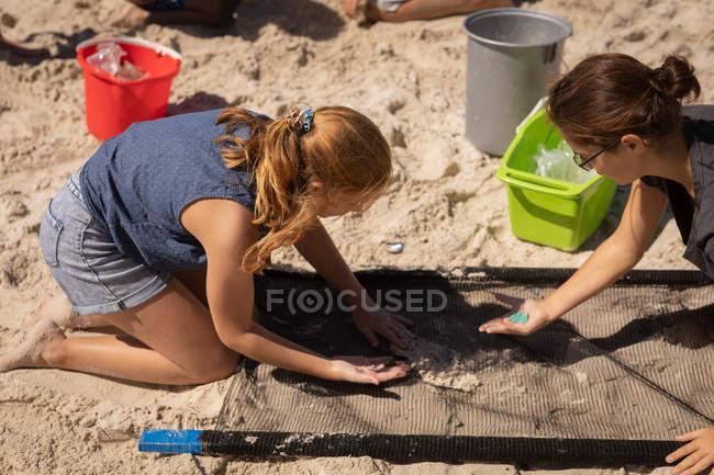 Hochwinkelansicht junger kaukasischer Freiwilligerinnen, die an einem sonnigen Tag mit einem Netz am Strand Abfall finden — Stockfoto