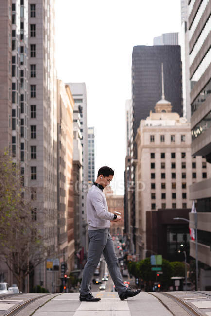 Side view of Asian man using smart watch and listening to music with wireless earphones while crossing the street — Stock Photo