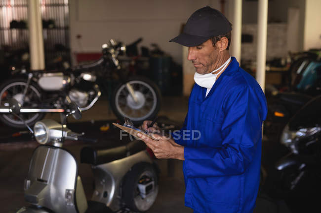 Side view of Caucasian bike mechanic maintaining automobile records on clipboard at garage — стокове фото