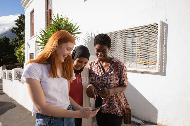 Vue de face de heureux amis mixtes femmes revivre des photos sur téléphone mobile dans la rue de la ville — Photo de stock