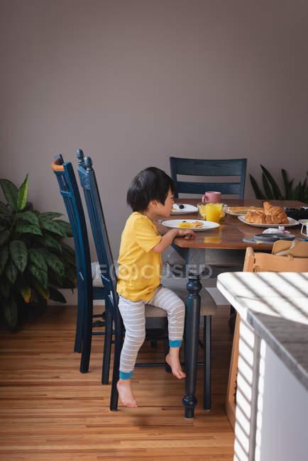 Вид сбоку на азиатского ребенка, сидящего на стуле во время завтрака на кухне дома — стоковое фото