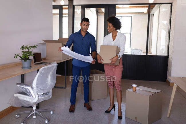 Front view of young Mixed-race business people move in a new office while they are discussing about plan — Photo de stock