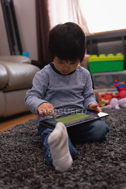 Vorderansicht eines kleinen asiatischen Jungen mit digitalem Tablet, während er zu Hause auf Teppich sitzt — Stockfoto