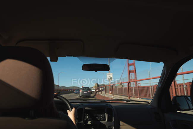 Woman driving car over golden gate bridge on a sunny day — Stock Photo
