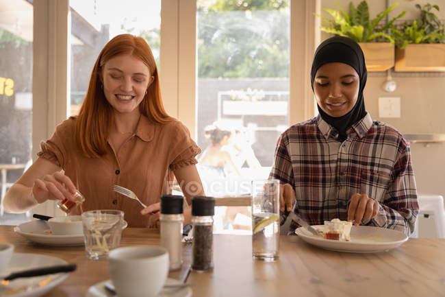 Vue de face de jeunes amies métisses interagissant les unes avec les autres tout en prenant le petit déjeuner au restaurant — Photo de stock