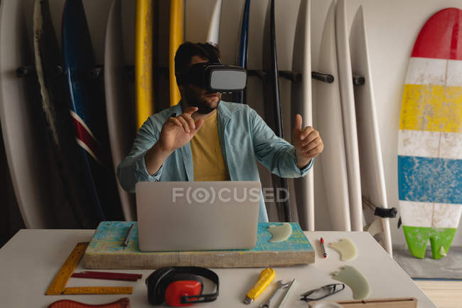 Front view of Caucasian man using virtual reality headset in a workshop — Stock Photo