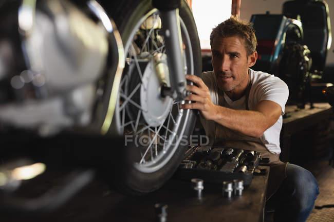 Front view of Caucasian bike Mechanic repairing bike in garage — стокове фото