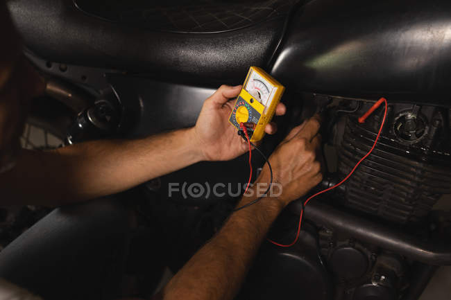 Mécanicien de vélo vérifier batterie de vélo avec multimètre dans le garage — Photo de stock