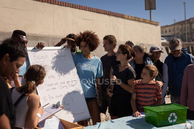 Frontansicht einer Gruppe von Multi-Ethnischen, die sich ein Board mit Freiwilligenregeln am Strand anschauen — Stockfoto