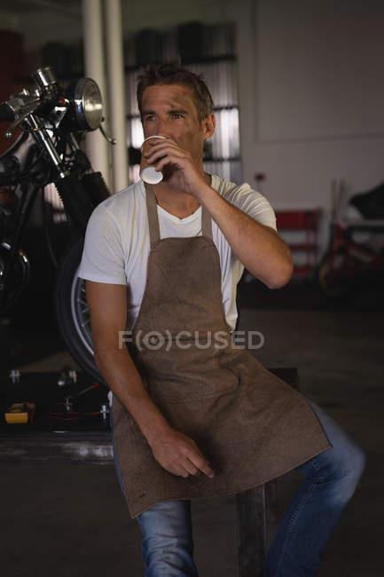 Front view of Caucasian bike mechanic sitting while having coffee in garage — Stock Photo