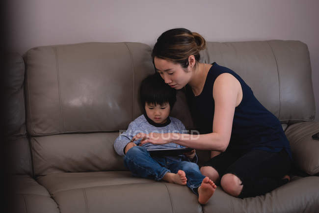 Vista frontal de la madre y el hijo asiáticos usando tableta digital mientras está sentado en el sofá en casa - foto de stock