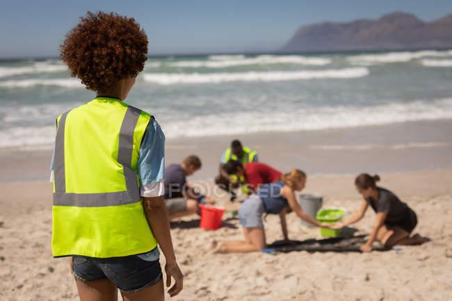Rückansicht der gemischten Rasse weibliche Freiwillige stehen am Strand, während sie die anderen Freiwilligen an einem sonnigen Tag — Stockfoto