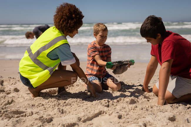 Frontansicht einer Gruppe von mehrethnischen Freiwilligen, die an einem sonnigen Tag den Strand putzen, während sie auf den Knien sitzen — Stockfoto