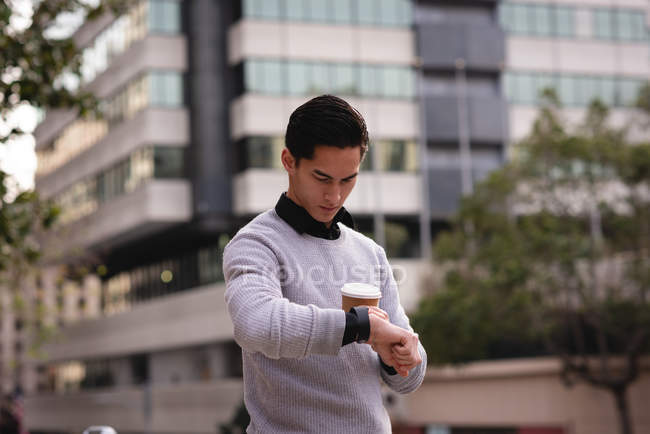 Vue de face de bel homme asiatique en utilisant la montre intelligente tout en prenant un café dans la rue — Photo de stock