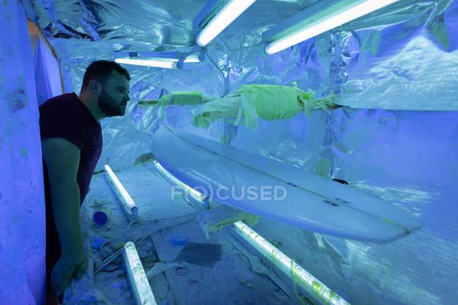 Вид збоку красивий Кавказький чоловік дивиться на дошку для серфінгу в спеціальній кімнаті УФ в майстерні — стокове фото
