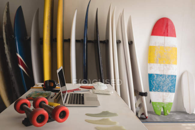 Colorful surfboards arranged with laptop on desk on foreground in a shop — Stock Photo