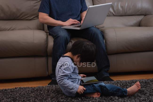 Unterteil des asiatischen Vaters mit seinem Laptop auf dem Sofa, während sein Sohn zu Hause ein digitales Tablet benutzt — Stockfoto