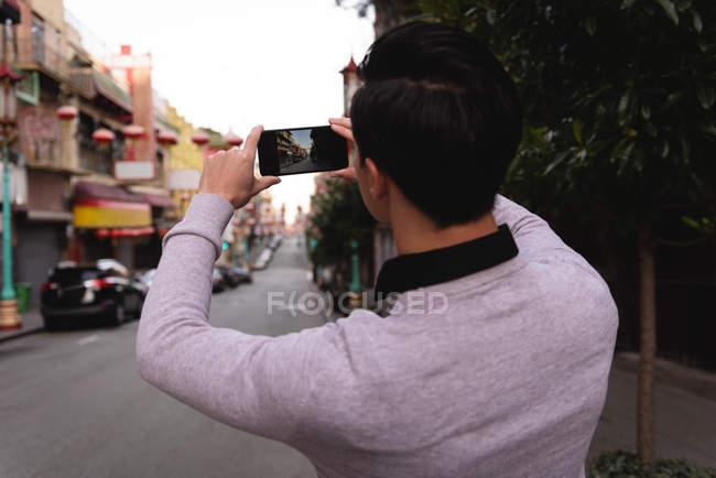 Vista posteriore dell'uomo asiatico che cattura foto della città dal telefono cellulare — Foto stock