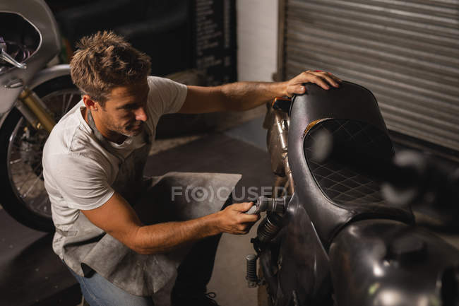 High angle view of Caucasian male bike mechanic checking bike with ratchet wrench in garage — стокове фото
