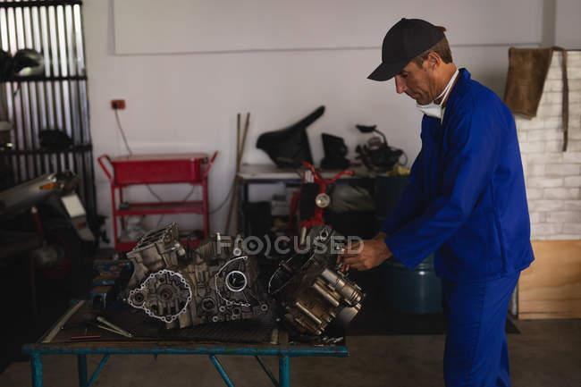 Вид збоку Кавказького велосипеда механік ремонт двигуна в гаражі — стокове фото