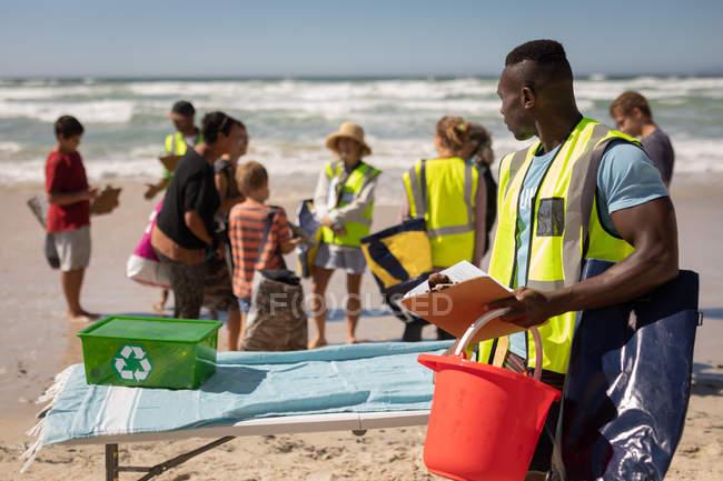 Frontansicht des afroamerikanischen männlichen Freiwilligen, der mit Eimer und Zwischenablage steht, während die anderen Freiwilligen hinter ihm am Strand sprechen — Stockfoto