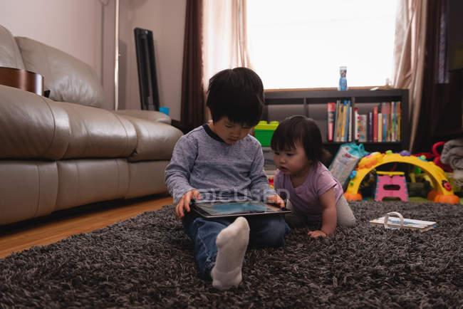 Вид з Азії брат і сестра дивляться разом на цифровий планшет у вітальні на дому — стокове фото