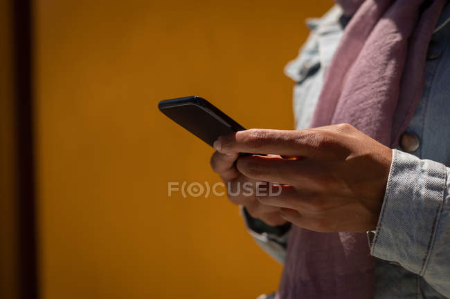 Mid section of woman using mobile phone on a sunny day — Stock Photo