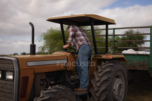 Rear view of senior Caucasian male farmer getting on the tractor on farm — Stock Photo