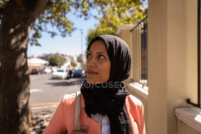 Vista frontale della donna meticolosa razza mista in piedi in strada in una giornata di sole — Foto stock
