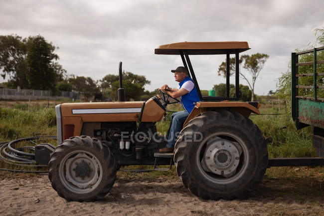 Side view of a senior Caucasian male farmer driving tractor on farm road — Stock Photo