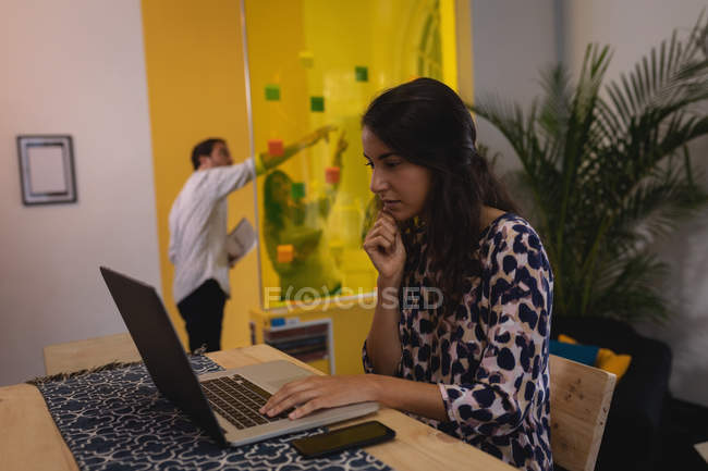 Side view of thoughtful mixed-race female executive working on laptop at desk in the office while business people discussing over sticky notes on glass wall — Stock Photo