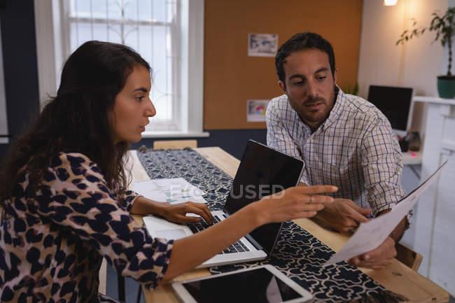 Vue de côté des cadres masculins et féminins divers attentifs discutant au-dessus du document dans le bureau — Photo de stock