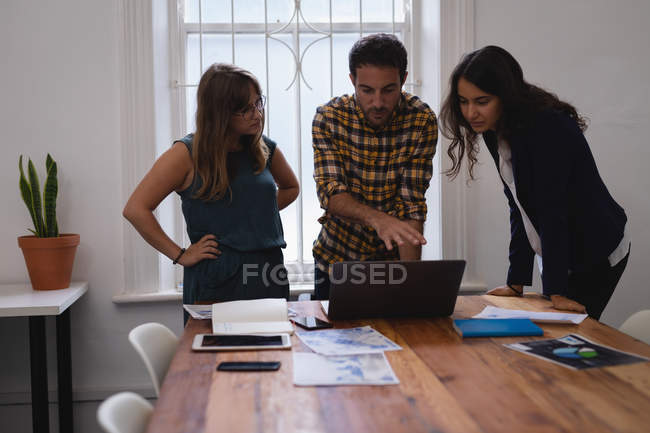 Front view of Diverse business people discussing over laptop at table in the office — Stock Photo