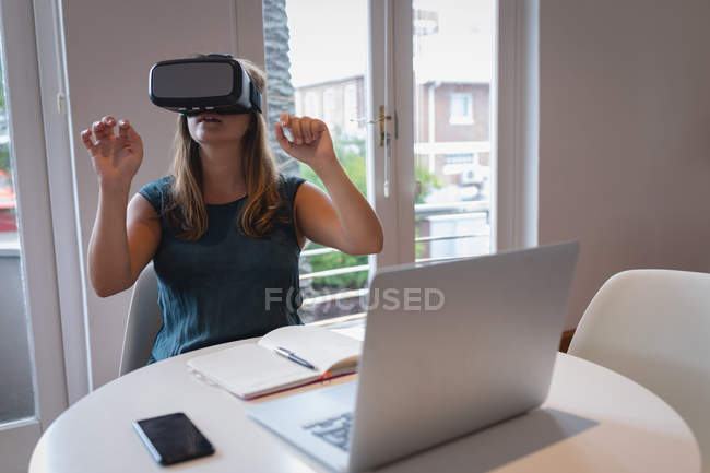 Front view of Caucasian woman using virtual reality headset at a table in the office — Stock Photo