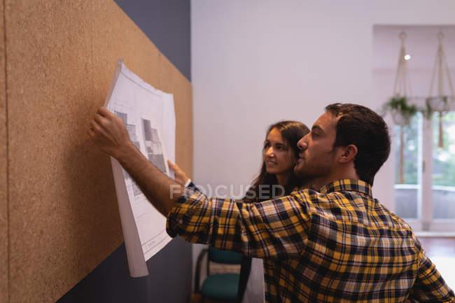 Вид с левой стороны кавказских бизнесменов, смотрящих на план, взаимодействуя друг с другом в офисе — стоковое фото