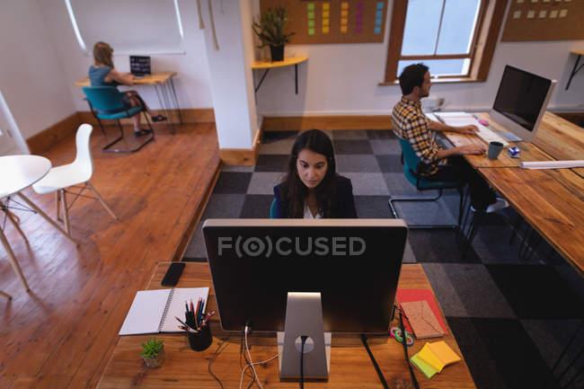 Vue avant de la femme d'affaires mixte attentive travaillant au-dessus de l'ordinateur au bureau tandis que des collègues travaillant derrière elle dans le bureau — Photo de stock