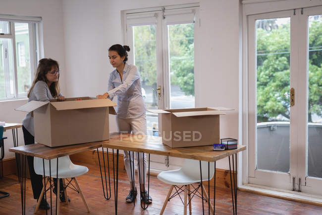 Side view of beautiful Diverse businesswomen packing cardboard boxes in the office — Stock Photo