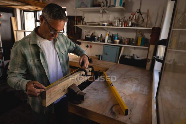 Vue latérale du menuisier mature caucasien attentif à l'aide d'une pince sur planche en bois dans l'atelier — Photo de stock