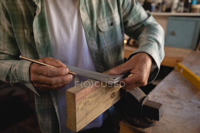Mid section of carpenter using try square on wooden plank in workshop - foto de stock