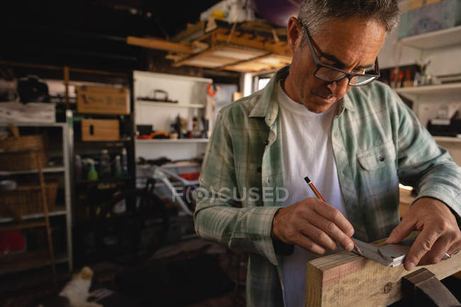 Front view of attentive Caucasian mature carpenter using try square on wooden plank in workshop — Stock Photo