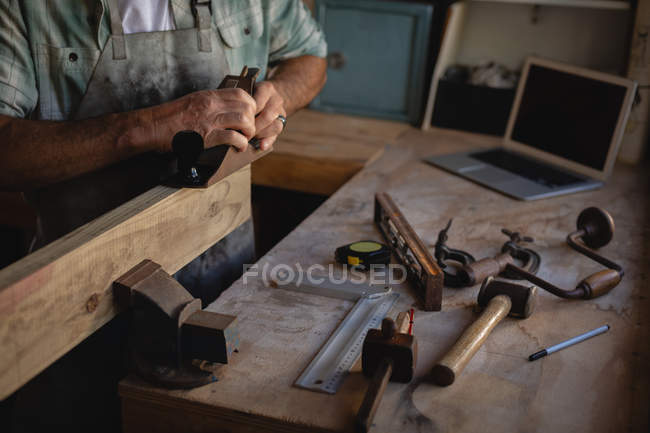 Mid section of carpenter using smooth plane on wooden plank in workshop - foto de stock