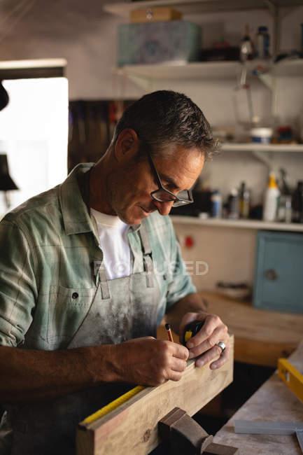Vista lateral do atencioso carpinteiro maduro caucasiano medindo uma prancha de madeira na oficina — Fotografia de Stock