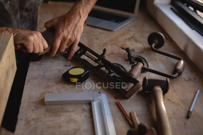 Mid section of carpenter holding smooth plane in workshop - foto de stock