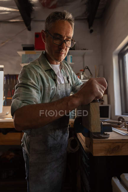 Front view of attentive mature Caucasian carpenter using smooth plane on wooden plank in workshop — Stock Photo