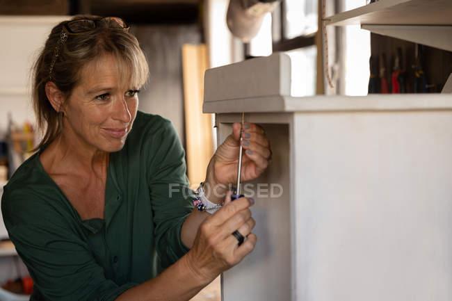Vorderansicht der aufmerksamen kaukasischen Tischlerin, die Schrank in Werkstatt repariert — Stockfoto