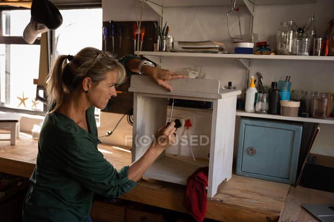 Seitenansicht einer kaukasischen Tischlerin, die Schrank in Werkstatt repariert — Stockfoto