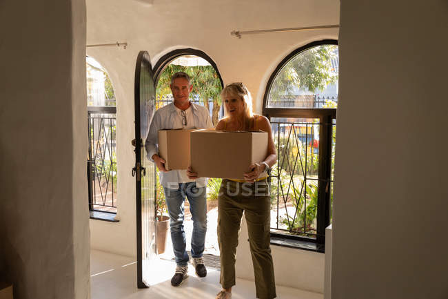Front view of happy mature Caucasian couple holding cardboard boxes while moving in new home — Stock Photo