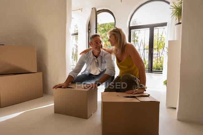 Vista frontal do casal caucasiano maduro feliz olhando um para o outro e relaxando depois de se mudar para sua nova casa — Fotografia de Stock