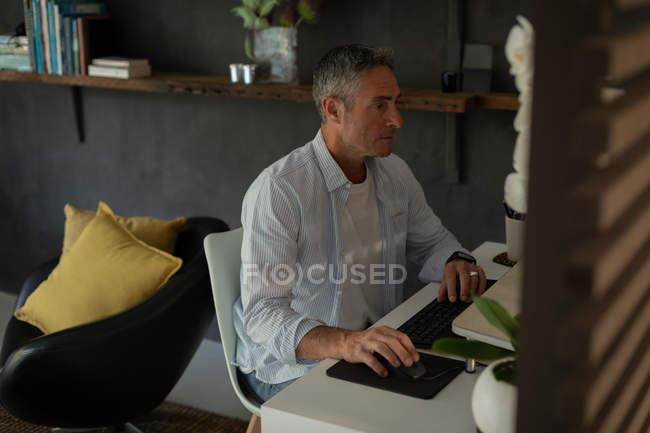 Vue latérale de mature homme caucasien en utilisant son ordinateur dans le salon à la maison — Photo de stock